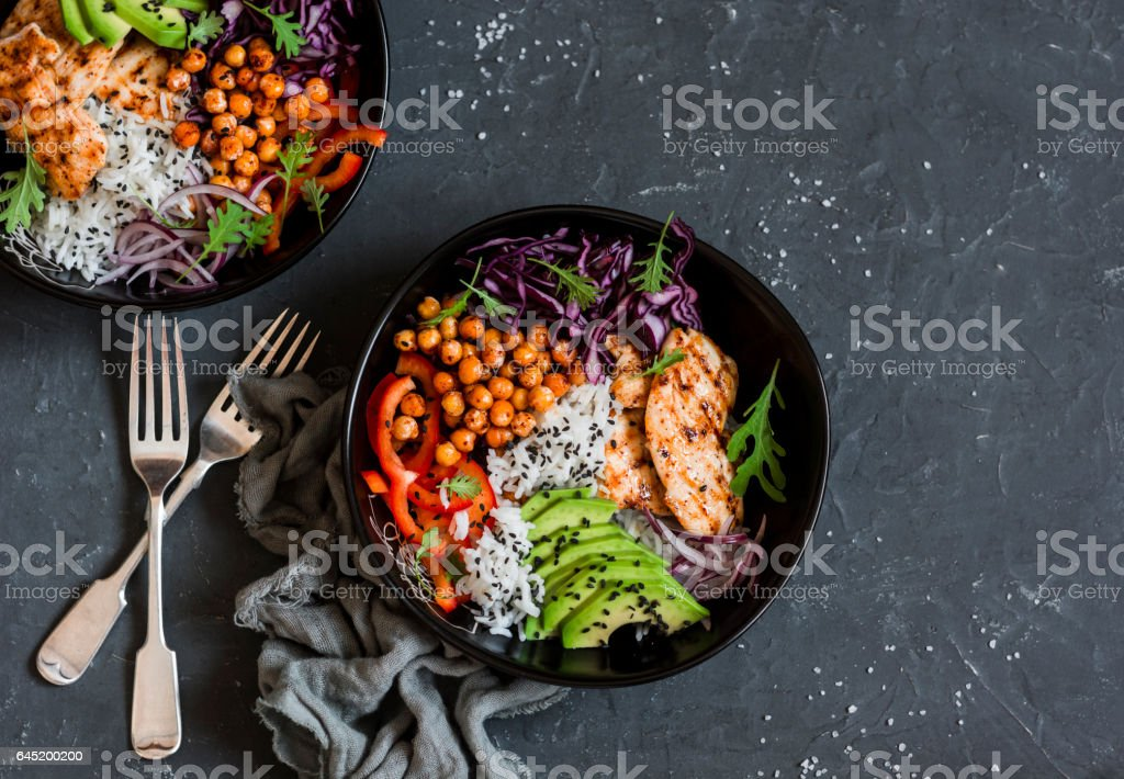 Grilled chicken, rice, spicy chickpeas, avocado, cabbage, pepper buddha bowl on dark background, top view. Delicious balanced food concept stock photo
