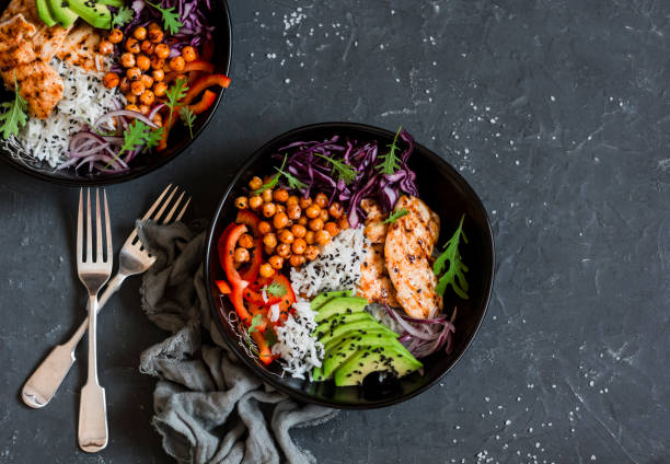 grilled chicken, rice, spicy chickpeas, avocado, cabbage, pepper buddha bowl on dark background, top view. delicious balanced food concept - chicken rice stock photos and pictures