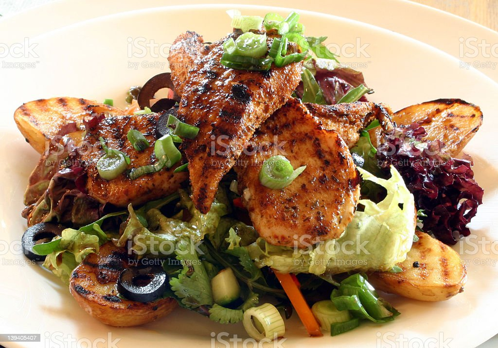 Grilled chicken salad with squash, scallions and olives stock photo