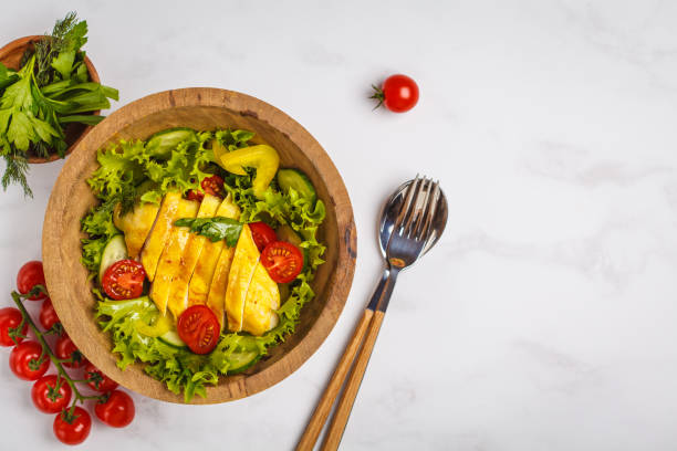 Grilled chicken salad with vegetables in a wooden bowl on a white background. Healthy balanced diet concept. stock photo