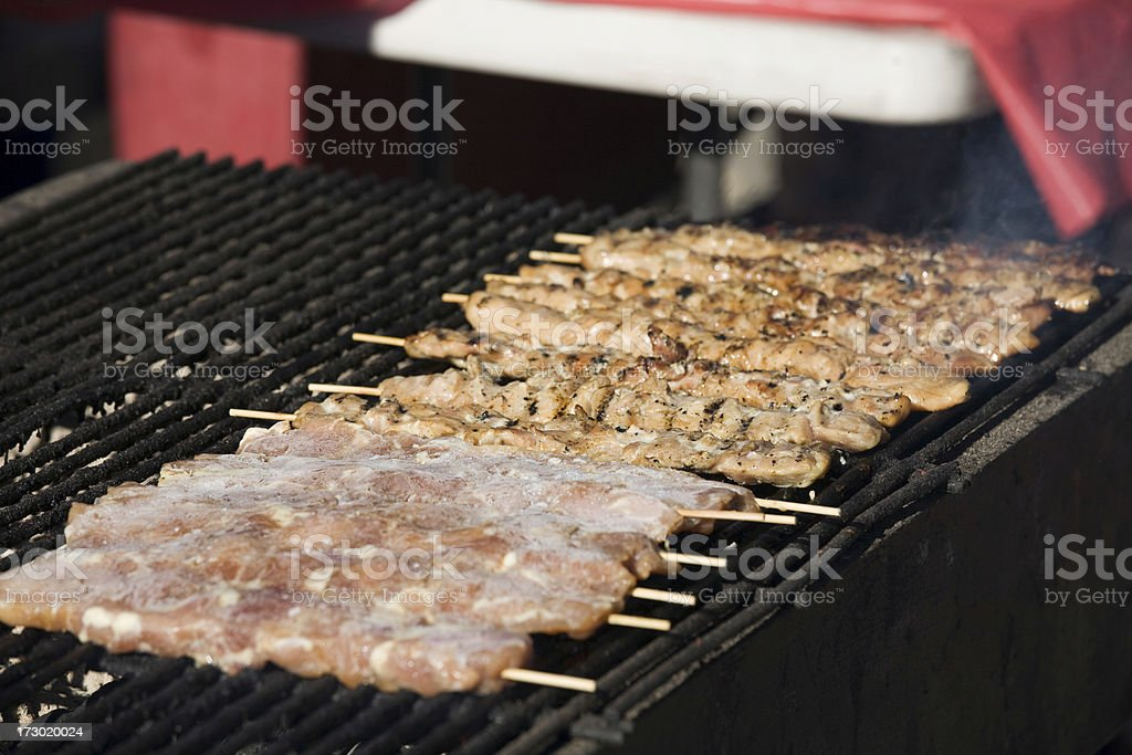 Grilled chicken satay skewers cooking on grill. royalty-free stock photo