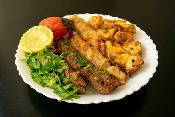 Grilled chicken shashlik, lamb, beef kofta kebab, vegetables, lemon on white plate on dark wooden background, close up stock photo