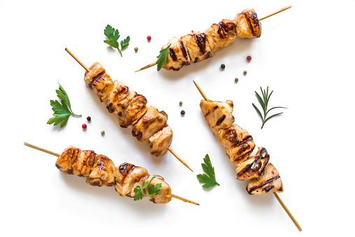 Grilled chicken skewers isolated on white background, top view. Meat pork, chicken or turkey shish kebab with herb and spices.