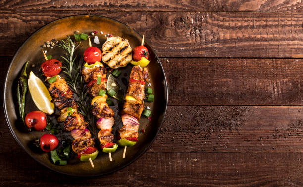 Grilled chicken skewers with spices and vegetables in a pan on wooden background stock photo