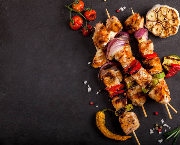 Grilled chicken skewers with spices and vegetables on stone black background stock photo