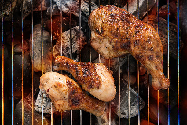Grilled chicken thigh over flames on a barbecue stock photo