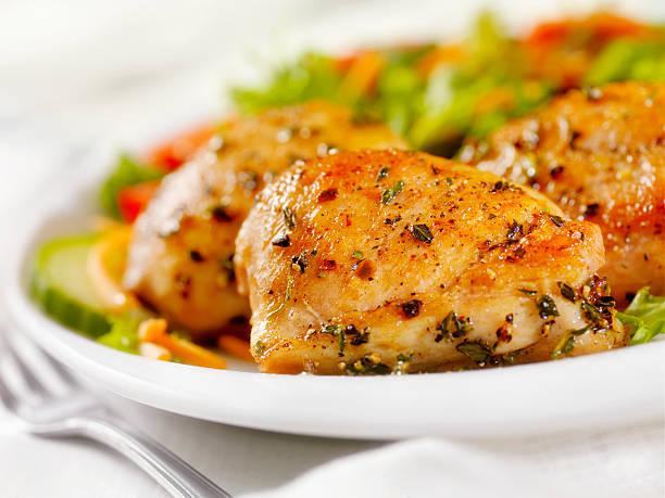cuisses de poulet grillé, une salade en accompagnement - poulet viande blanche photos et images de collection
