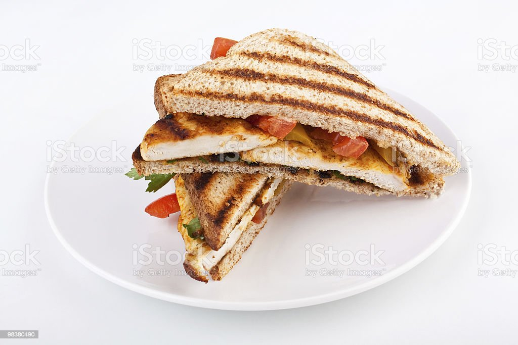 A grilled chicken toasted sandwich on a white plate royalty-free stock photo