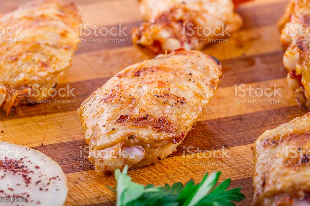 Grilled Chicken Wings and Legs On Wood Plate stock photo