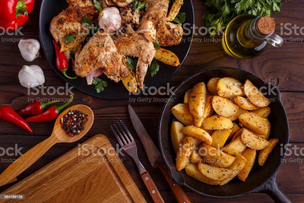 Grilled chicken wings, baked potatoes, herbs and spices on kitch stock photo