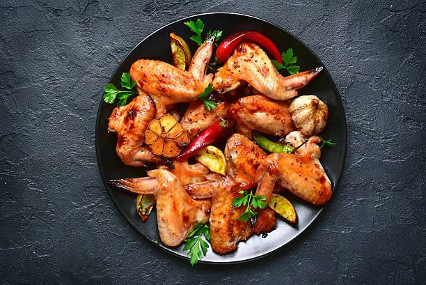 grilled chicken wings on a black plate.top view. - gewürz für gegrilltes hähnchen stock-fotos und bilder