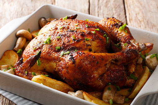 grilled chicken with mushrooms and potatoes close-up in a baking dish. horizontal