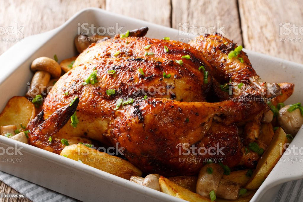 grilled chicken with mushrooms and potatoes close-up in a baking dish. horizontal stock photo
