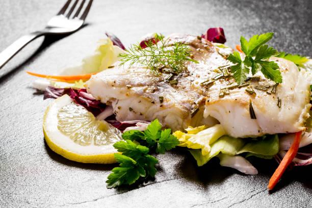 grilled cod fillet with salad on black slate plate - cod imagens e fotografias de stock