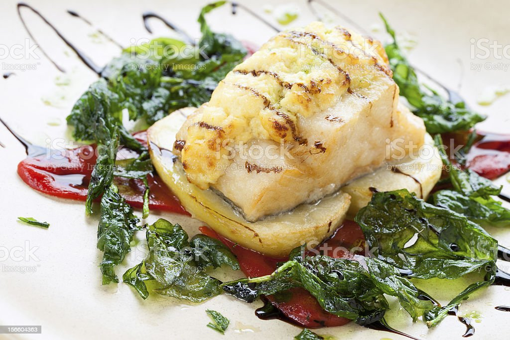 Grilled cod fish with spinach leaves. royalty-free stock photo