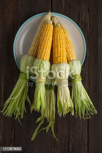 Corn on the cob on a white dish, top view