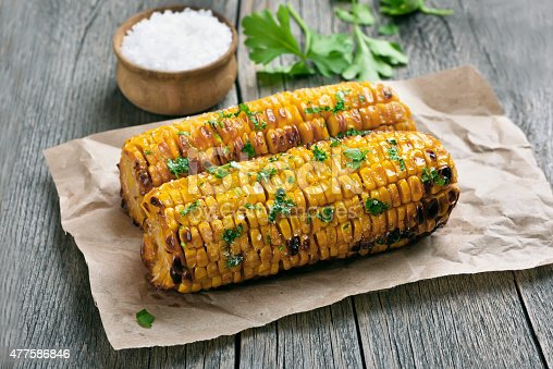 Grilled corn cobs on paper over rustic table