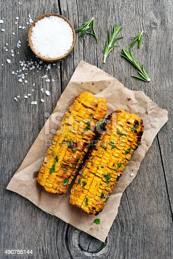Grilled corn cobs on wooden background, top view