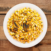 Top view of white dish full of grilled corn kernels on it