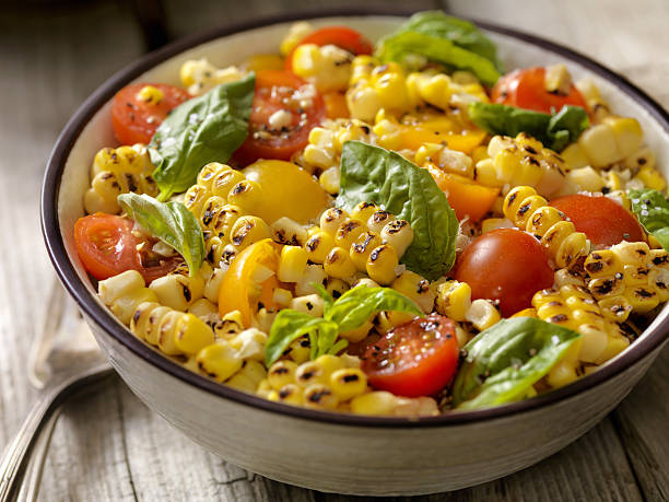 grilled corn salad with tomatoes and basil - beikost stock-fotos und bilder