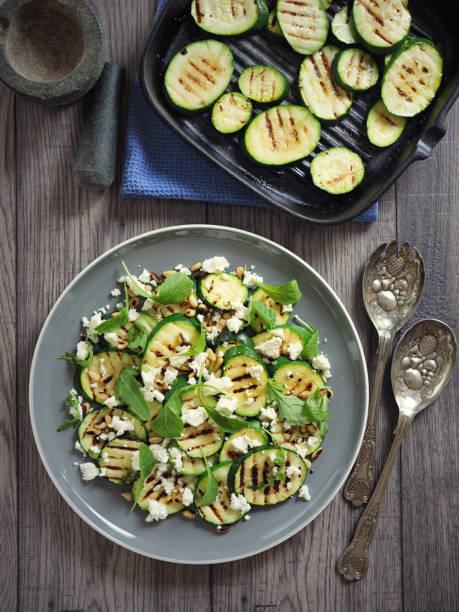 gegrilde courgette met pijnboompitten en feta kaas salade - courgette stockfoto's en -beelden