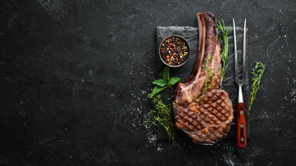 Bife, ervas e especiarias grelhados da carne do cowboy em um fundo de pedra preto. Churrasco. Vista de cima. Espaço livre para o texto. - foto de acervo