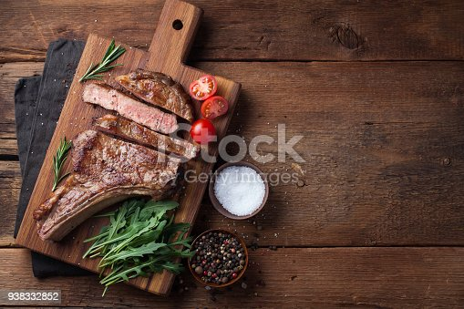 istock Grilled cowboy beef steak, herbs and spices on a rustic wooden background. Top view with copy space for your text 938332852