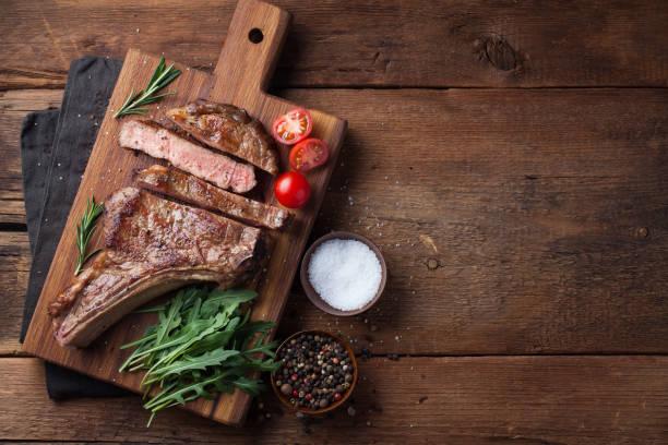 gegrilde cowboy biefstuk, kruiden en specerijen op een rustieke houten achtergrond. bovenaanzicht met kopie ruimte voor uw tekst - ribeye biefstuk stockfoto's en -beelden