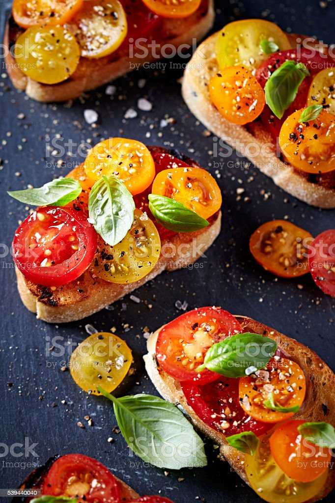 Grilled Crostinis with Fresh Cherry Tomatoes and Basil stock photo