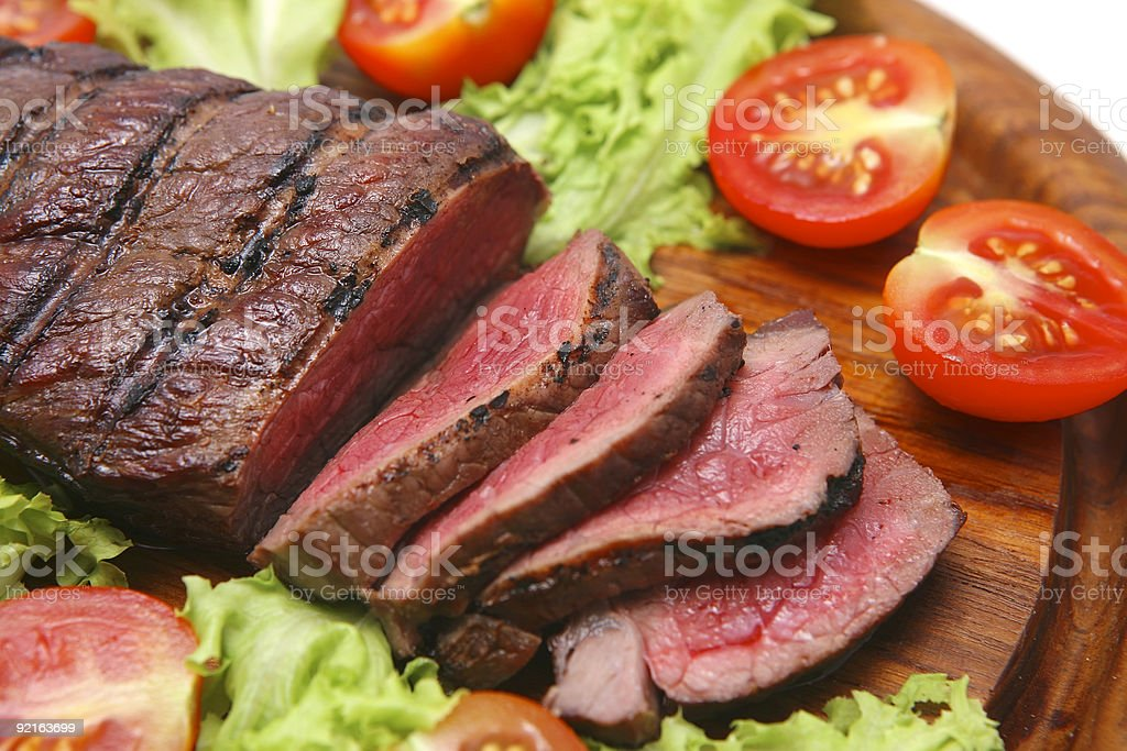 Grilled cut red meat surrounded by tomatoes and lettuce stock photo