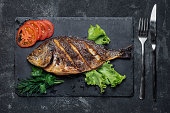 Grilled dorada on a black stone tray served food top view.