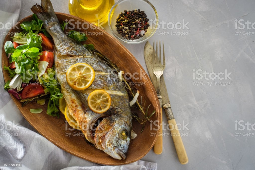 Grilled Dorado with lemon, thyme, rosemary and fresh salad стоковое фото