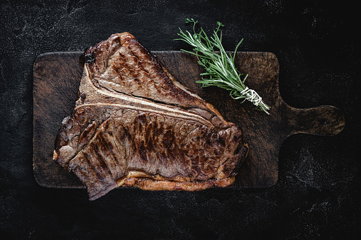 istock Grilled Dry Aged Beef T-bone Steak on Vintage Cutting Board 1157088257