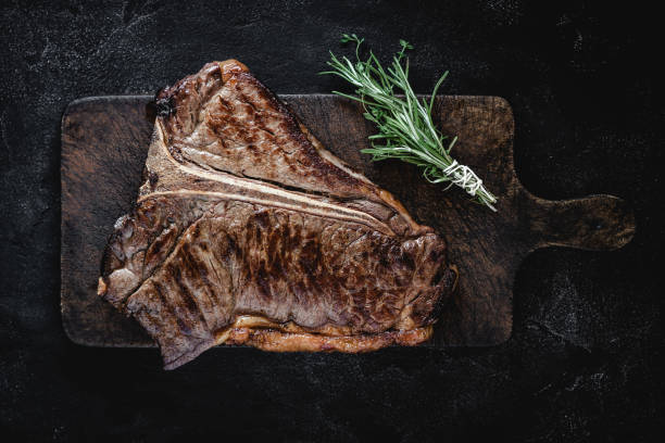 gegrillte trocken gealtert rindfleisch t-bone steak auf vintage schneidebrett - wie alt werden kühe stock-fotos und bilder