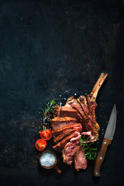 Grilled dry aged tomahawk beef steak sliced stock photo