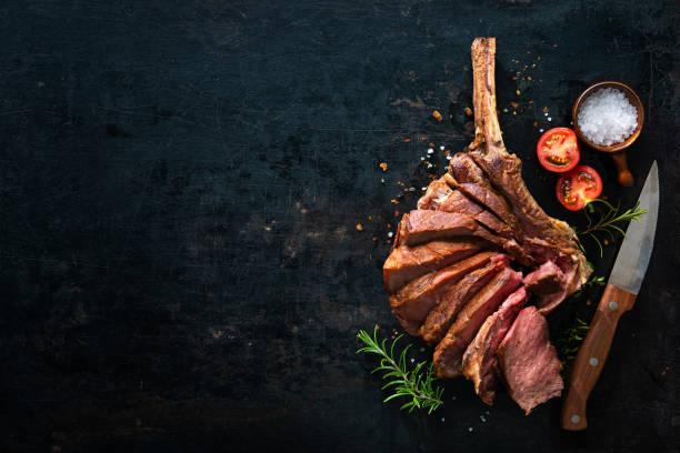 Grilled dry aged tomahawk steak sliced as close-up stock photo