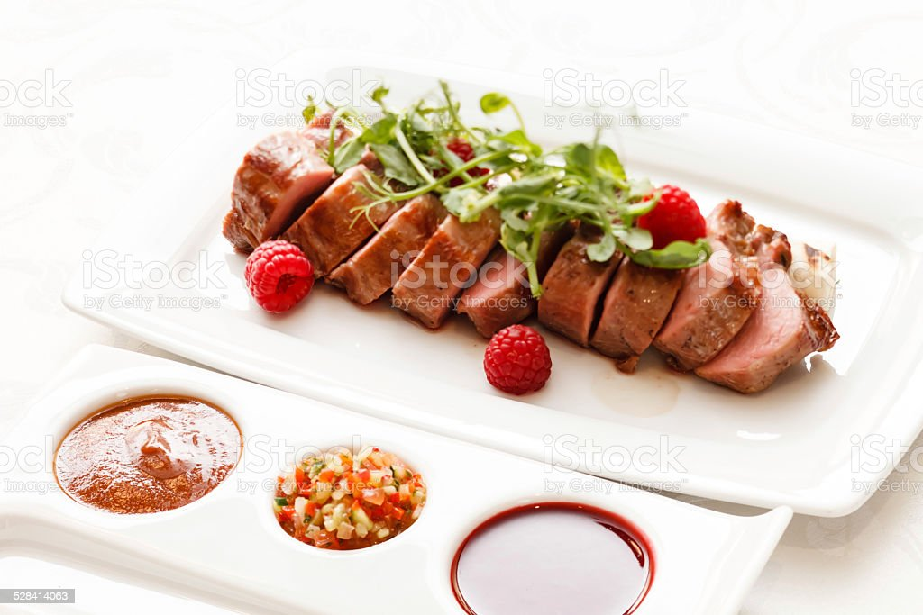 Grilled duck breast covered with sweet red fruit sauce - Stock image .