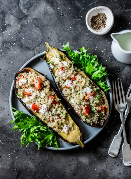 Gegrillte Auberginen gefüllt mit Couscous, Tomaten, Cilantro mit Joghurt-Sauce auf dunklem Hintergrund, Top-Ansicht – Foto