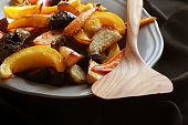Grilled fall seasonal vegetables on plate over a dark background .