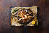 Grilled Fish Dorado on metal grill grid with lemon and rosemary