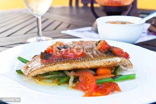Delicious grilled snapper fillet on vegetables, a bowl of soup and a glass of white wine on a table of an outdoor restaurant.
