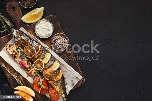Baked fish on wooden cutting board, top view, copy space on black slate