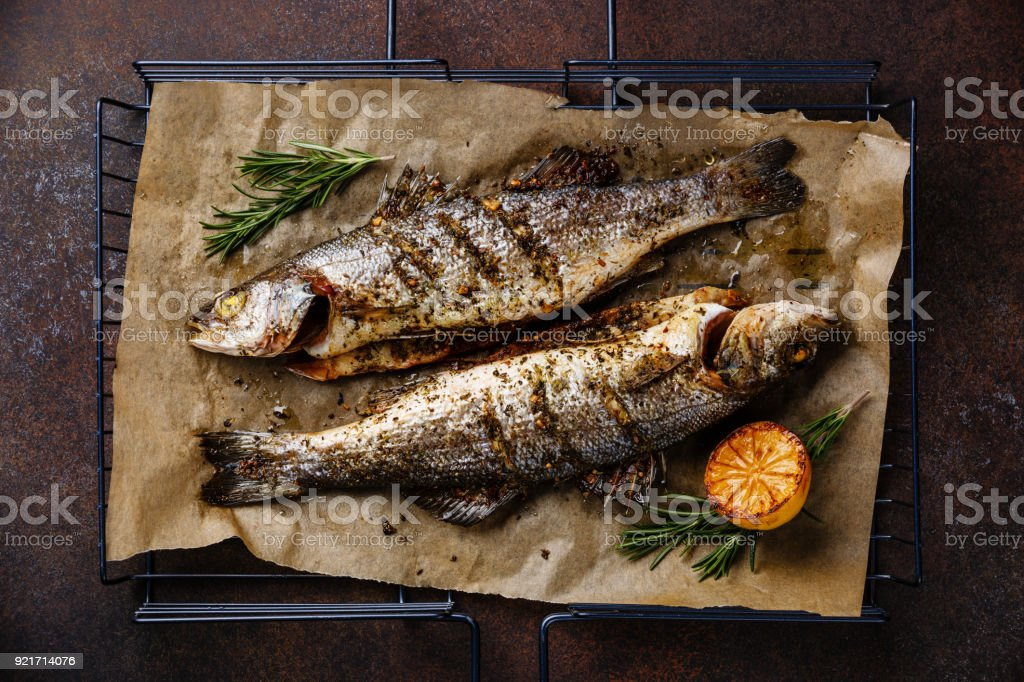 Grilled Fish Sea bass on grill with lemon and rosemary stock photo