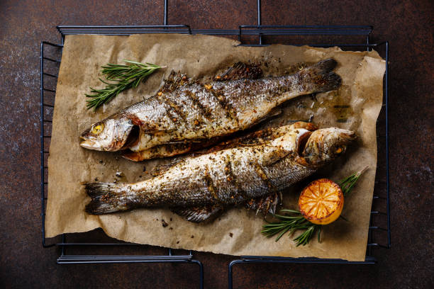 grilled fish sea bass on grill with lemon and rosemary - fish stock pictures, royalty-free photos & images
