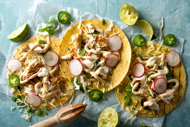 Grilled Fish Tacos Delicious tacos with grilled fish, cilantro, lime, cabbage, carrot, jalapeno and radish with mexican chili crema sauce. taco stock pictures, royalty-free photos & images