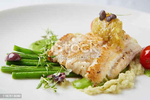 Gourmet grilled fish dish served in up-market restaurant.