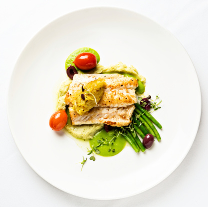 An overhead view of grilled white fish served with lentil puree and a selection of lightly-cooked vegetables and cherry tomatoes, for a delicious and healthy meal. Isolated on white.