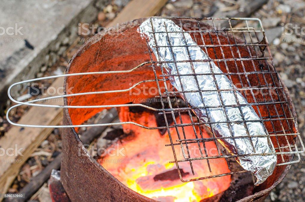 Grilled fish wrapped in foil on the stove. foto de stock libre de derechos