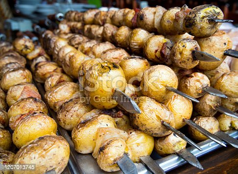 Grilled fresh potato tubers strung on skewers