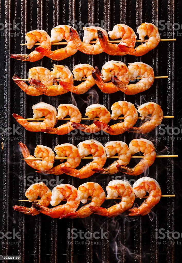 Grilled fried Prawns on skewers on grill stock photo